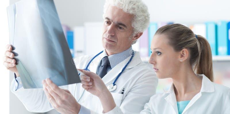 Radiolog sprawdza promieniowanie rentgenowskie z jego asystentem zdjęcie stock