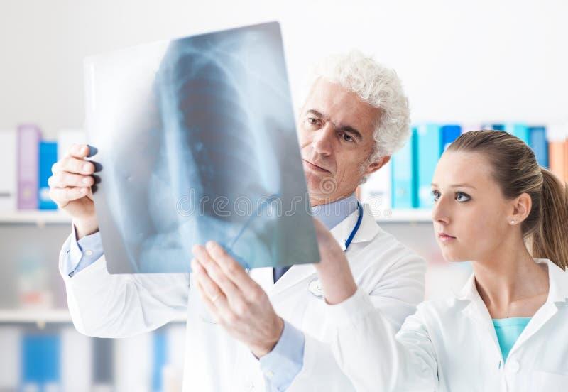 Radiolog sprawdza promieniowanie rentgenowskie z jego asystentem obraz stock