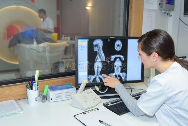Radiologe, der das Verfahren überwacht lizenzfreie stockfotos