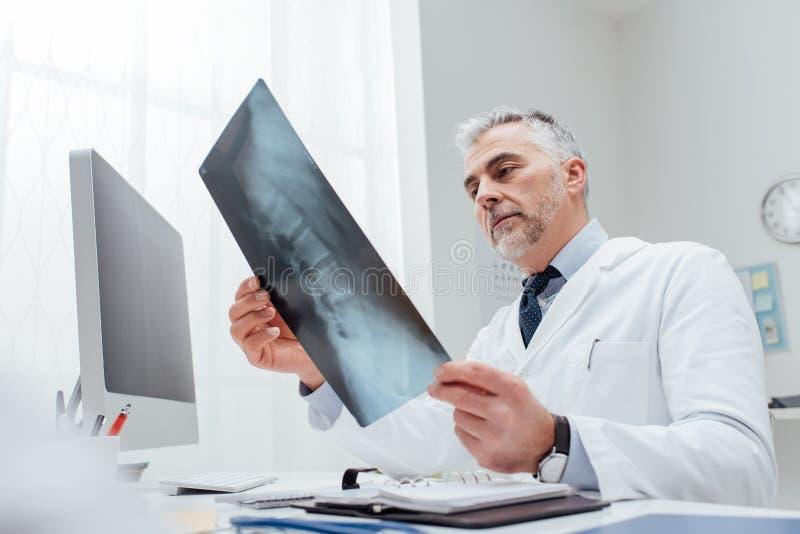 Radiologe, der ein Röntgenstrahlbild überprüft lizenzfreie stockbilder