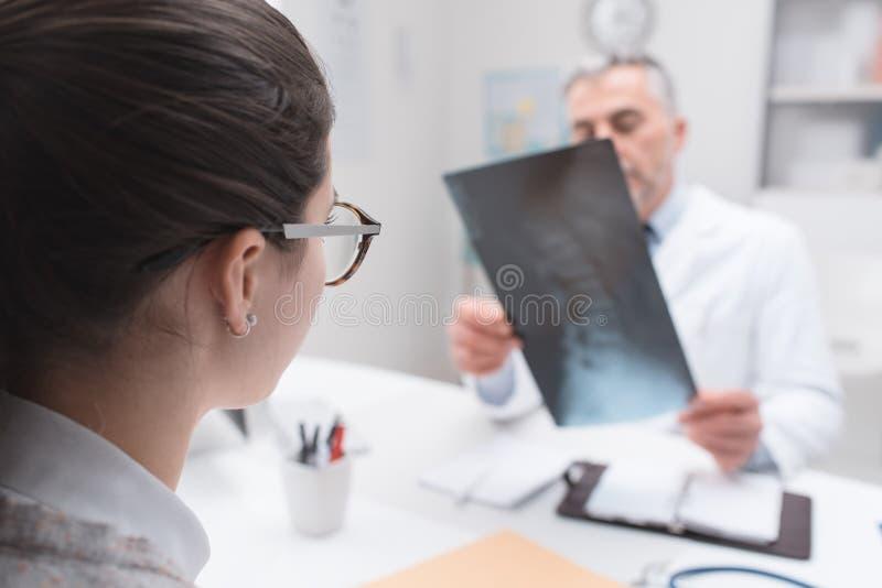 Radiologe, der ein Röntgenstrahlbild überprüft lizenzfreie stockfotografie