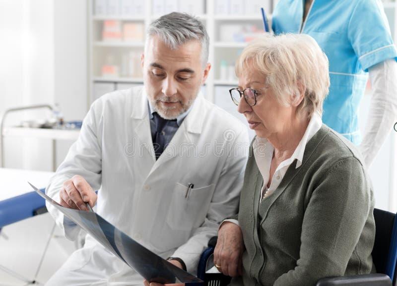 Radiologe, der ein Röntgenstrahlbild mit einem älteren Patienten überprüft stockbilder