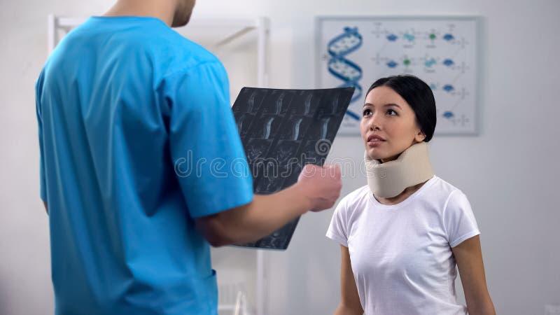 Radiologe mit informierendem Patienten des Röntgenstrahls über Ergebnisse, Dame, die mit Hoffnung hört stockfotos