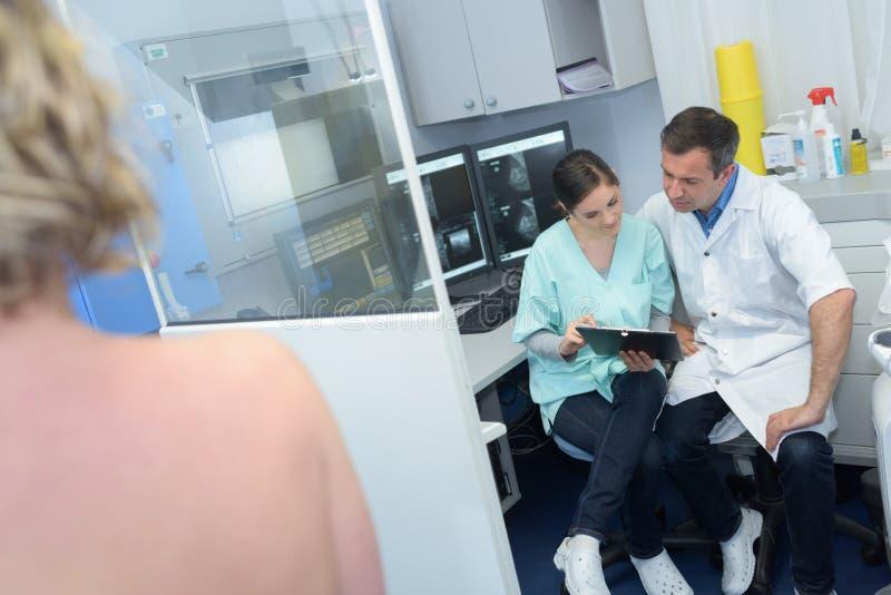 Radiologie medisch personeel in de naakte schouder van besprekingspatiënten in voorgrond stock afbeelding
