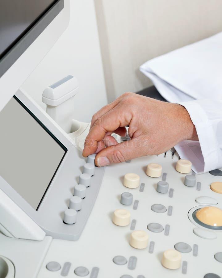 Radiologist Operating Ultrasound Machine. Close up of male radiologist's hand operating ultrasound machine stock image