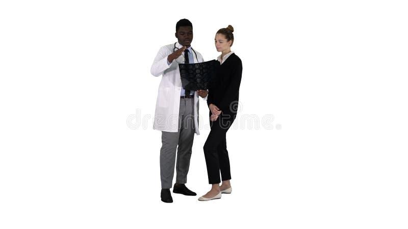Radiologista de visita da jovem mulher para o exame do raio X de seu cérebro no fundo branco imagem de stock