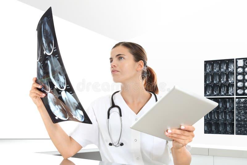 Radiologkvinna som kontrollerar röntgenstrålen, med minnestavlan, sjukvård arkivfoton