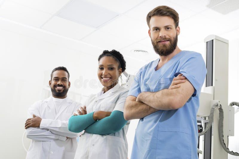 Radiologues de sourire tenant des bras croisés dans la chambre d'examen images stock