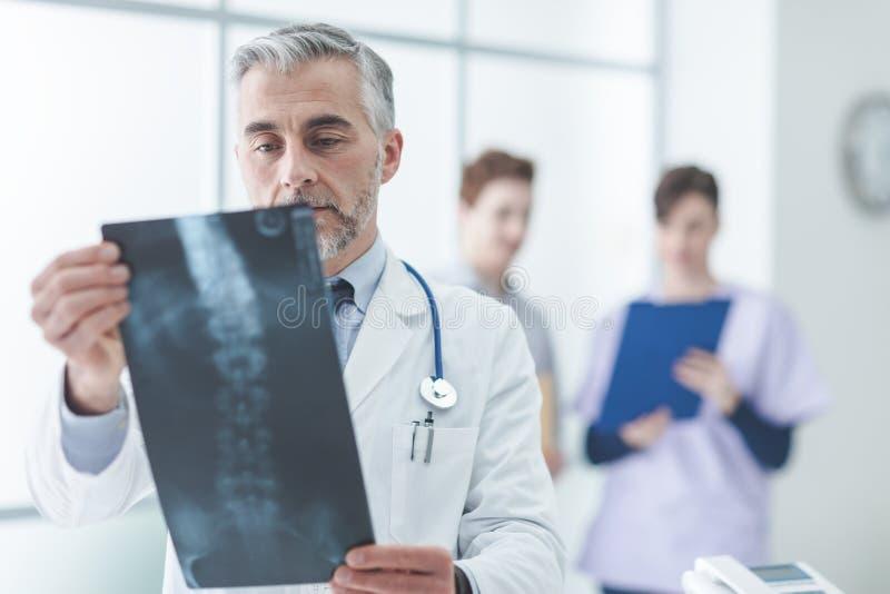Radioloog die de röntgenstraal van een patiënt onderzoeken royalty-vrije stock foto