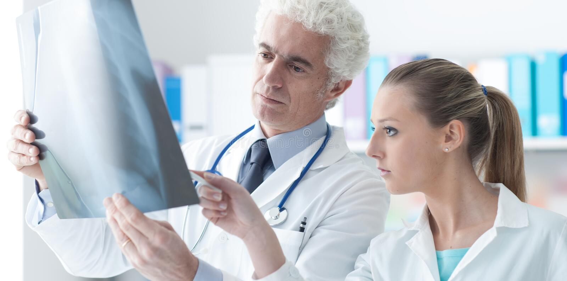 Radioloog die een röntgenstraal met zijn medewerker controleren stock foto