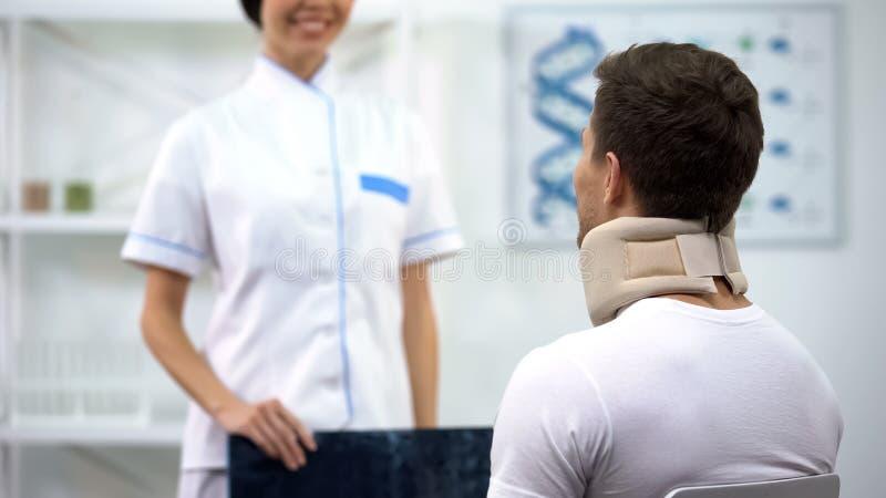 Radioloog die patiënt in goed het onderzoeksresultaat van de schuim cervicaal kraag informeren stock afbeelding