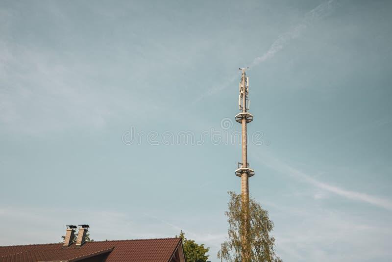 Radiomast för mobiltelefonnätverkstornen ovanför en bostads- byggnad in i den blåa himlen i ett bostadsområde royaltyfria bilder