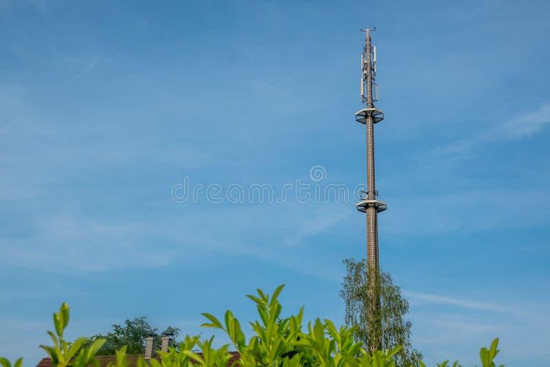 Radiomast f?r mobiltelefonn?tverkstornen ovanf?r en bostads- byggnad in i den bl?a himlen i ett bostadsomr?de arkivfoton