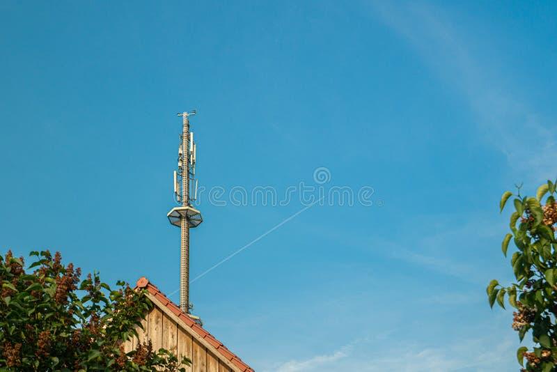 Radiomast f?r mobiltelefonn?tverkstornen ovanf?r en bostads- byggnad in i den bl?a himlen i ett bostadsomr?de arkivfoto