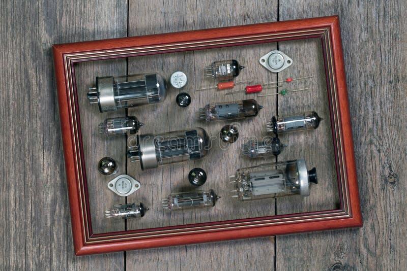 Radiorör och elektroniska delar i en ram på en träflik arkivfoto