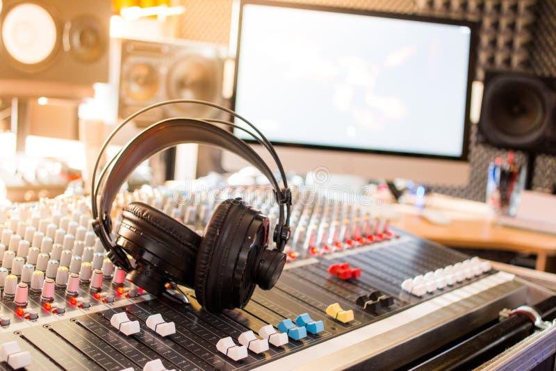 Radiostation: Hörlurar på ett blandareskrivbord i en yrkesmässig solid anteckna studio royaltyfria foton