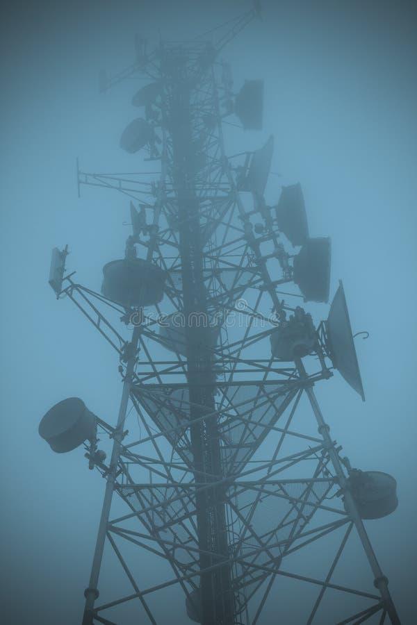 Radiotorn bland tjock kall mist royaltyfria bilder