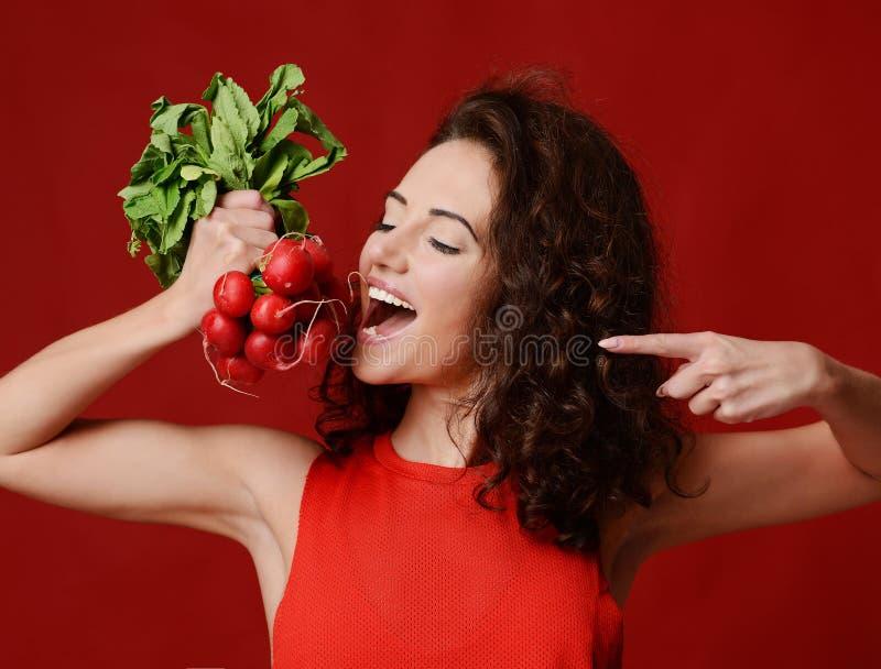 Radis frais de jeune de sport prise assez gaie de femme avec les feuilles de vert et le doigt de pointage dieting images stock