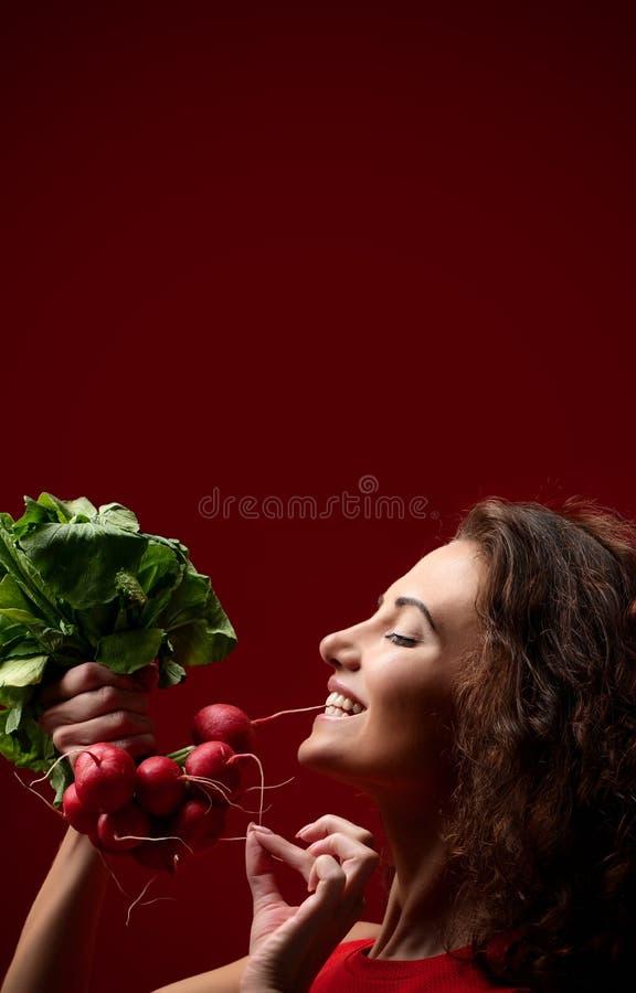Radis frais de prise de femme avec les feuilles vertes dieting Concept sain de consommation sur le fond rouge pour l'histoire d'i image stock