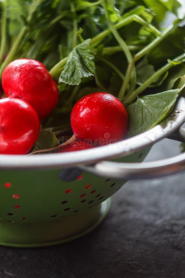 Radis rouge juteux frais lavé dans une passoire sur un fond foncé photo stock