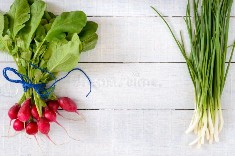 Radis rouges frais et jeunes oignons verts sur le fond en bois blanc photo libre de droits