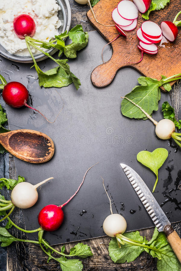 Radishes preparation ingredients. Food background with fresh garden colorful Radishes , wooden spoon, kitchen knife, old cutting stock image