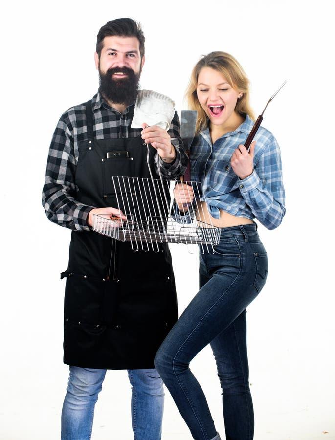 Radość grilla styl kucharstwo Ładna kobieta i brodaty mężczyzny mienia kucharstwo ucieramy Szczęśliwa para używa kulinarną siatkę zdjęcie royalty free