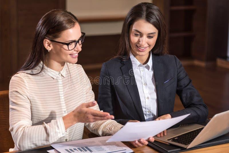 Radośni żeńscy koledzy dyskutuje projekt w biurze obraz stock