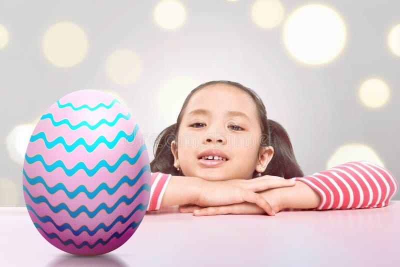 Radośni azjatykci małego dziecka znaleziska Easter jajka zdjęcie stock