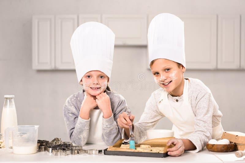 radośni dzieci szczotkuje ciastka na wypiekowej tacy w fartuchach zdjęcia royalty free