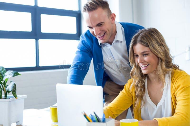 Radośni koledzy używa laptop w biurze obraz stock
