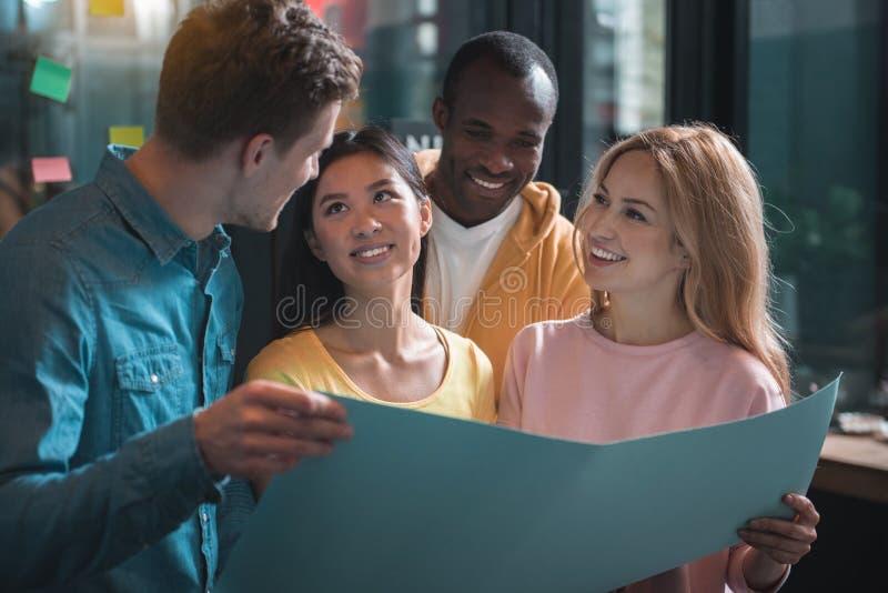 Radośni młodzi coworkers dyskutują ich projekt obrazy royalty free