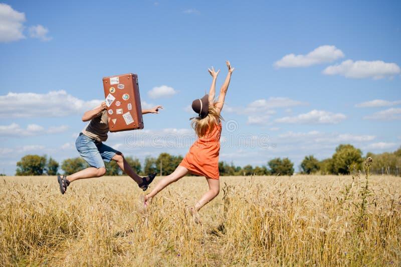 Radośni potomstwa dobierają się mieć zabawę w pszenicznym polu Z podnieceniem mężczyzna i kobiety bieg z retro rzemienną walizką  obrazy royalty free