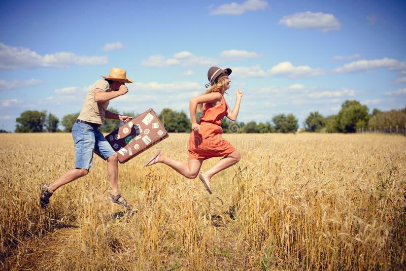 Radośni potomstwa dobierają się mieć zabawę w pszenicznym polu Z podnieceniem mężczyzna i kobiety bieg z retro rzemienną walizką  zdjęcia stock