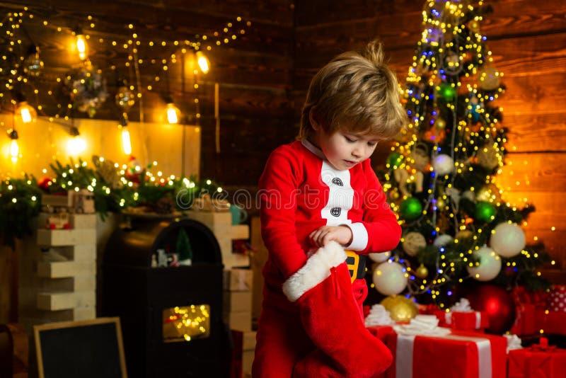 Rado?? i szcz??cie Dzieci?stwo momenty Dzieciak ch?opiec Santa chwyta bo?ych narodze? prezent Bo?enarodzeniowy po?czochy poj?cie  zdjęcia royalty free