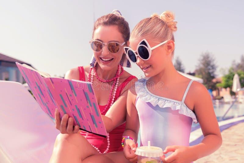 Radosna ładna matka i córka czyta książkę wpólnie obrazy royalty free