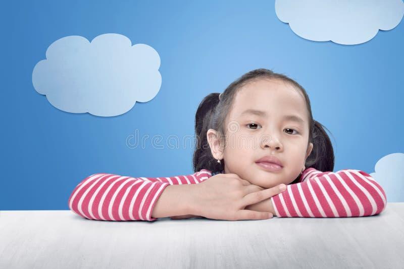 Radosna azjatykcia mała dziewczynka relaksuje na stole obraz stock