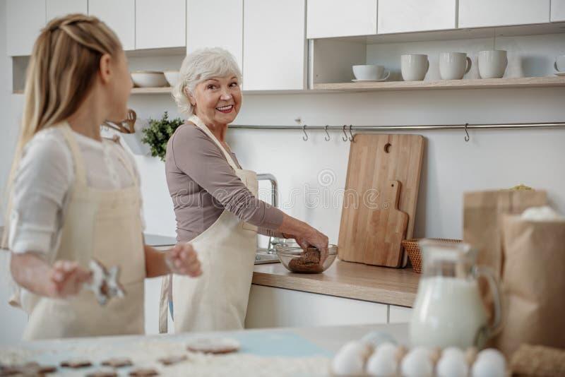 Radosna babcia robi ciastu z jej wnuczką w kuchni fotografia stock