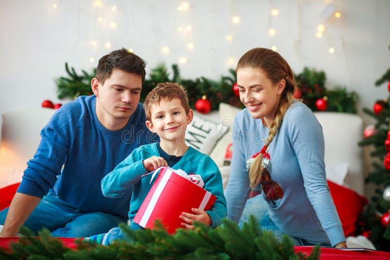 Radosna chłopiec z rodzicami otwiera nowego roku prezenta pudełko przy bożymi narodzeniami do domu obraz royalty free