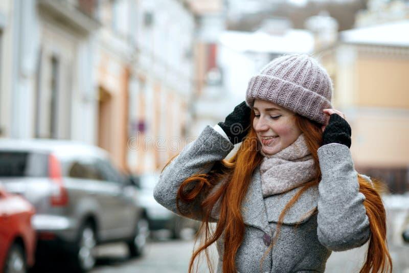 Radosna czerwona z włosami dziewczyna jest ubranym ciepłej zimy odprowadzenia odzieżowego puszek obrazy royalty free