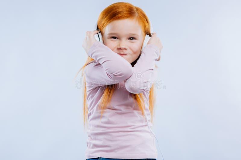 Radosna czerwona z włosami dziewczyna słucha muzyka fotografia stock