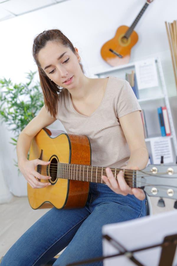 Radosna dziewczyna bawić się gitarę w domu obrazy royalty free