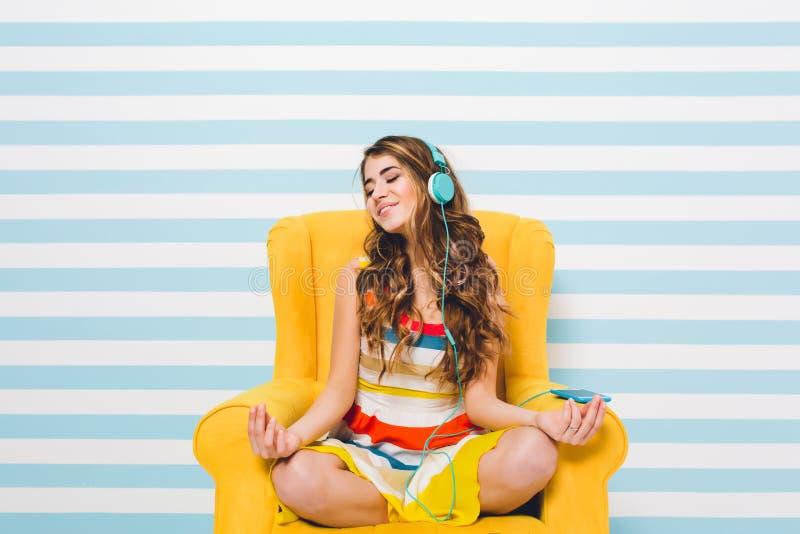 Radosna dziewczyna medytuje podczas gdy siedzący w lotosowej pozie na błękitnym pasiastym tle ?adna m?oda kobieta w kolorowej suk obraz royalty free