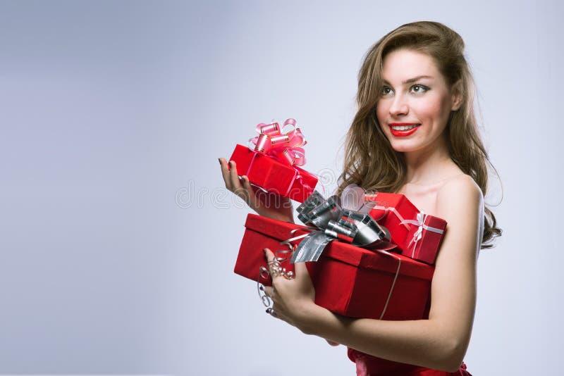 Radosna dziewczyna w czerwieni sukni z prezentami obrazy royalty free