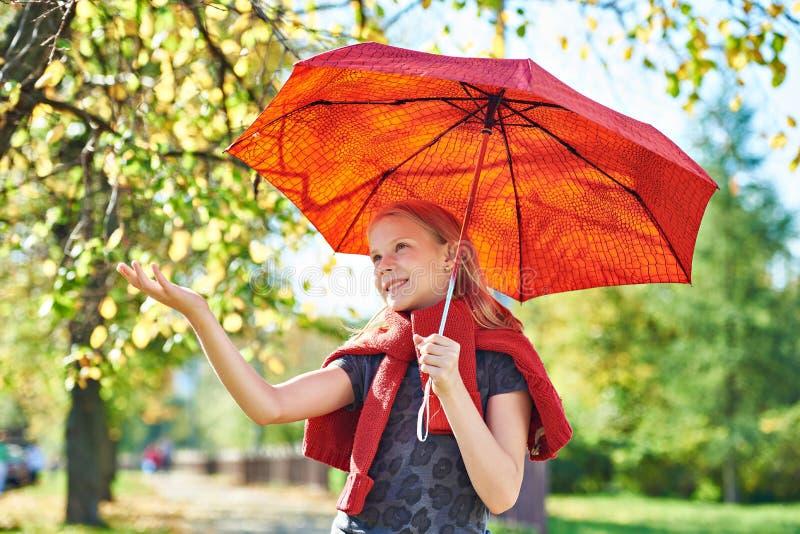 Radosna dziewczyna z czerwonym parasolem w jesień parku na słonecznym dniu zdjęcie stock