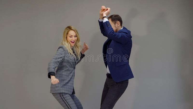 Radosna kobieta i mężczyzna w garniturach tanczy na popielatym tle zdjęcie royalty free