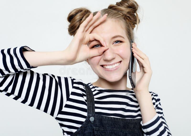 Radosna kobieta ono uśmiecha się, demonstrujący białych zęby, patrzeje kamerę przez palców w zadowalającym gescie fotografia royalty free