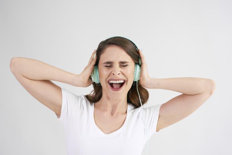 Radosna kobieta s?ucha muzyka z he?mofonami obraz stock