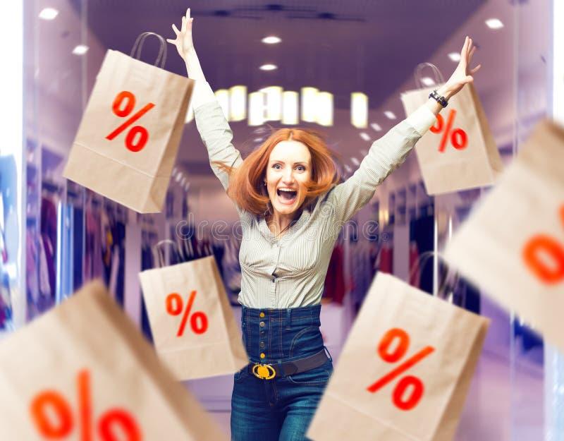 Radosna kobieta wśród sprzedaży papierowych toreb w sklepie obraz stock