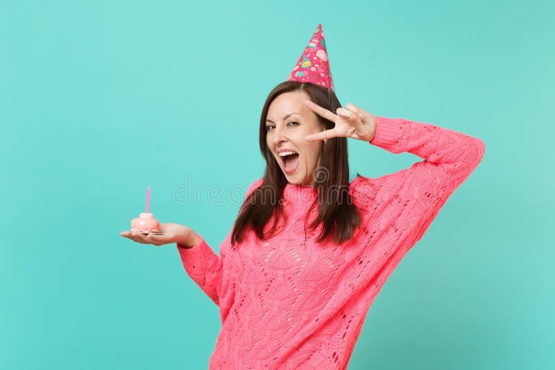 Radosna kobieta w trykotowego różowego puloweru usta zwycięstwa urodzinowym kapeluszowym utrzymuje szeroko otwarty pokazuje znaku zdjęcie royalty free